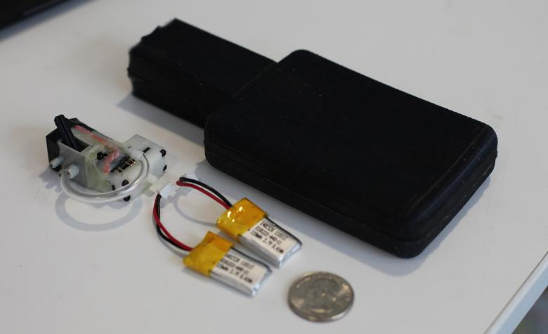 Mobile Jamming Platform: Our Mobile Jamming Platform (MJP) enables pneumatic jamming in a compact, low-power, battery-driven form factor. The MJP consists of a jamming volume, micro air pump, valve and LiPo batteries. (U.S. quarter for scale)
